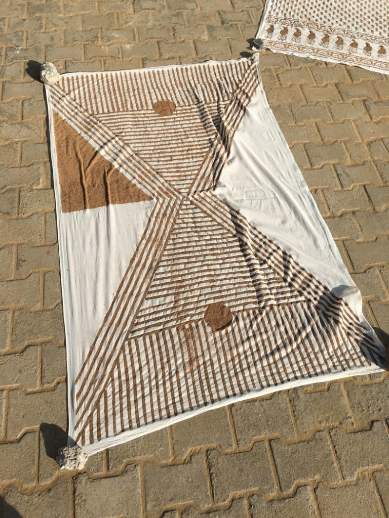 My finish mud resist printed fabric laying in the sun to dry before dyeing.