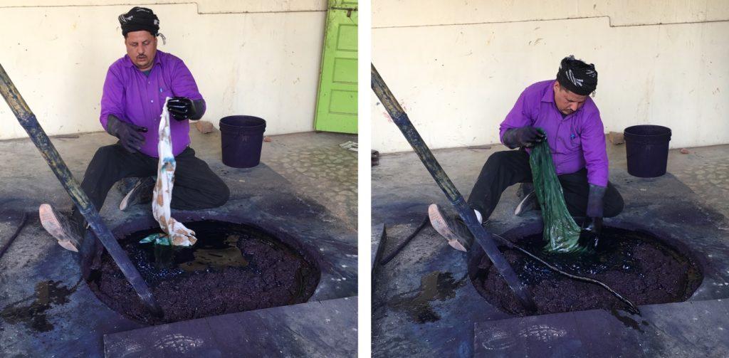 Ein Arbeiter tunkt den bedruckten Stoff in das Indigobad. Der Stoff ist zunächst dunkelgrün, wird aber durch Sauerstoffaussetzung nach wenigen Minuten blau.