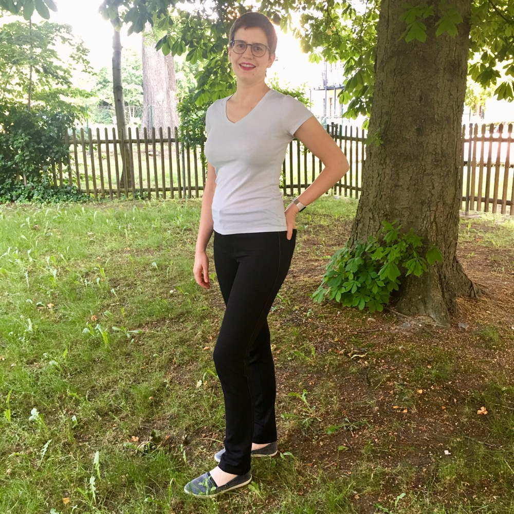 A woman standing in a backyard at a quarter profile. She is wearing a white t-shirt and black pants, ponte ginger jeans.
