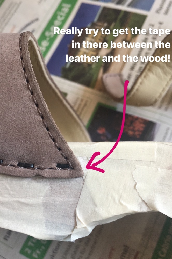 A detail view of a clog covered in masking tape, showing that the tape is layered between the leather and wood to protect the wood from the suede dye.