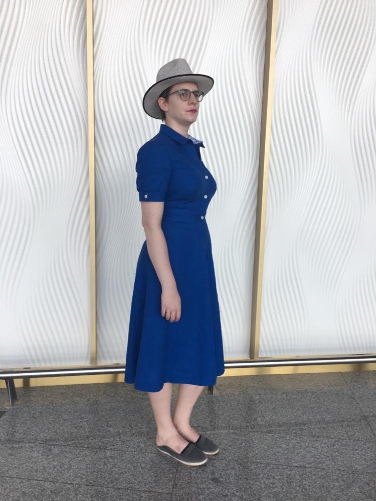 Eine Frau steht vor einem hellen Hintergrund und trägt ein kornblumenblaues Kleid, Colette Penny.