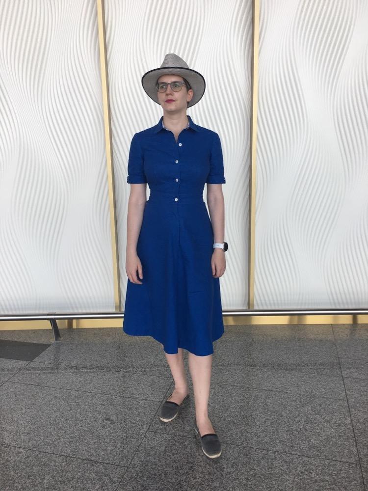 Eine Frau steht vor einem hellen Hintergrund und trägt ein kornblumenblaues Kleid, Colette Penny. Das Kleid ist wadenlang und hat leicht gepuffte Ärmel.