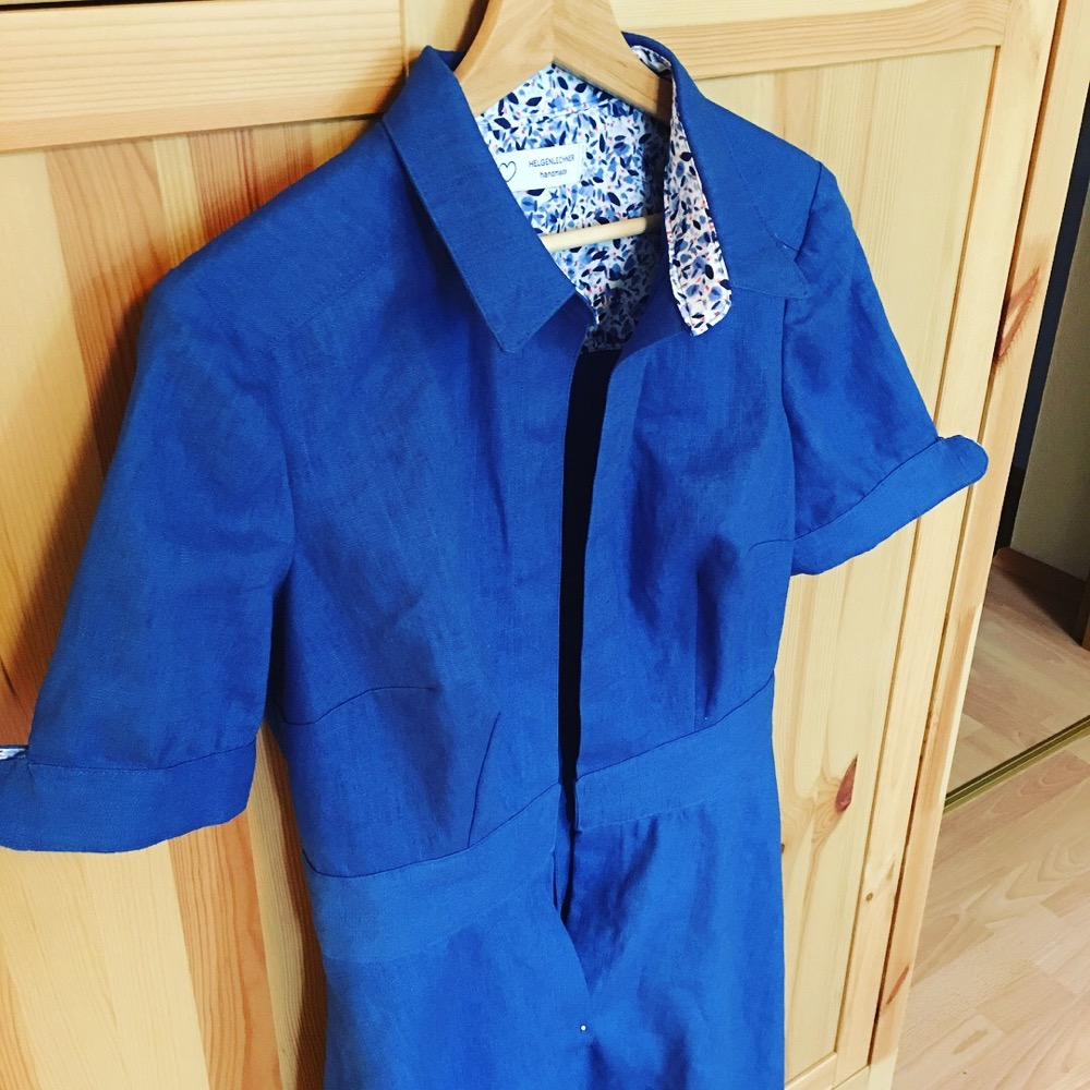 A blue shirt dress, Colette Penny, on a hanger. It is almost finished, but the buttons and buttonholes are still missing.