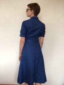 Eine Frau ist von hinten zu sehen. Sie steht vor einer weißen Wand und trägt ein blaues Hemdblusenkleid.