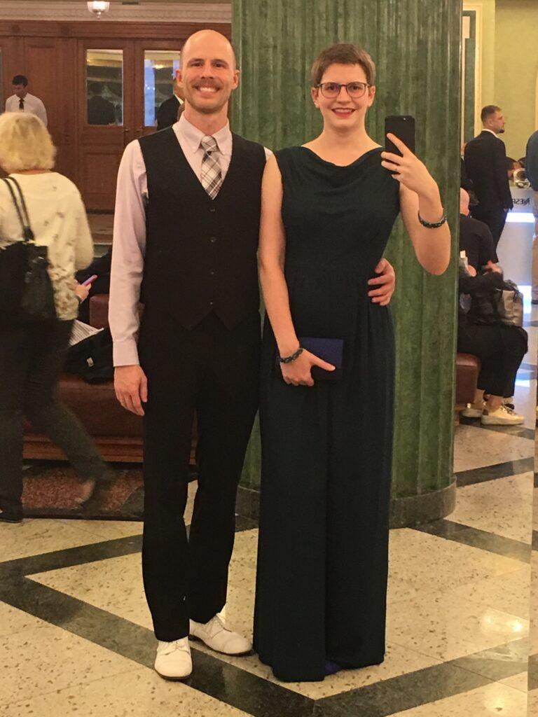 Bettina und ihr Ehemann zu sehen in einem Spiegelselfie. Er trägt eine Weste, Krawatte und violettes Hemd, sie ihr selbstgenähtes Abendkleid.