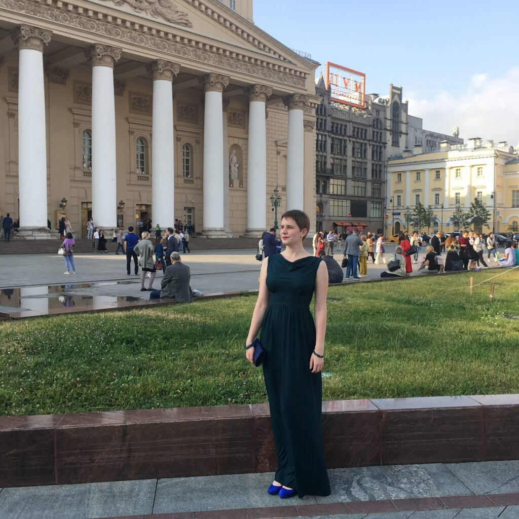 Bettina stands in front of the Bolshoi Theater in Moscow wearing her dark green selfsewn evening gown and cobalt blue accessories.