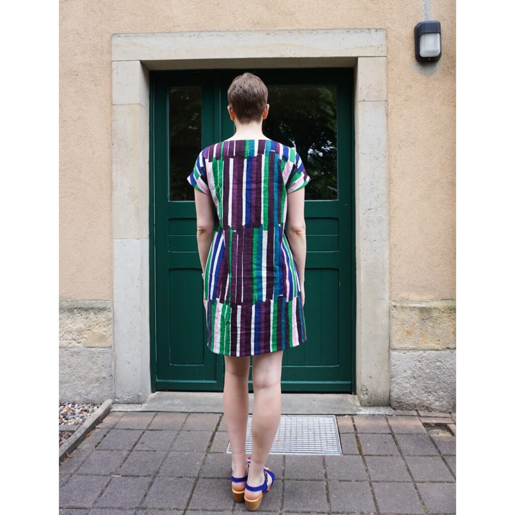 Bettina, seen from behind, standing in front of a green doorway wearing her Nani IRO double gauze shift dress.