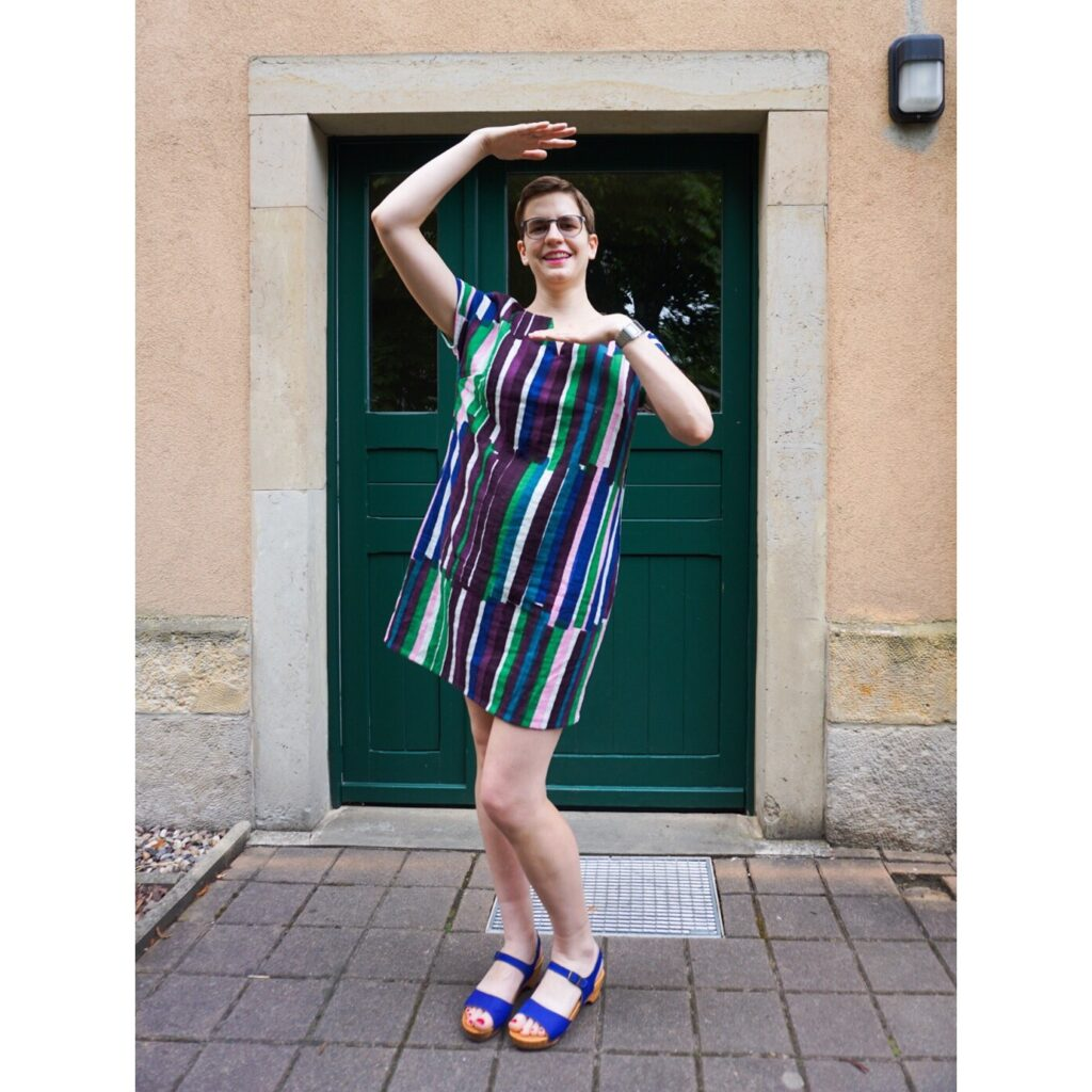 Bettina standing in front of a green doorway wearing her Nani IRO double gauze shift dress. She is smiling and framing her face with her hands.