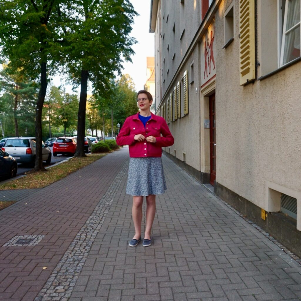 Bettina stands on a sidewalk and buttons up her pink jean jacket. She is seen from the front and looks off to the side.