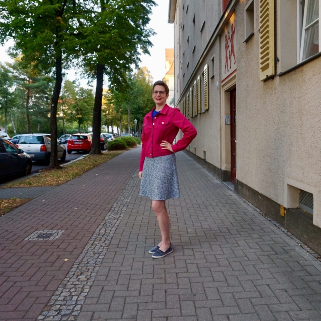Bettina stands on a sidewalk. She has one hand on her hip and is seen in a quarter profile. She's wearing her pink jean jacket and a heathered gray A-line skirt.