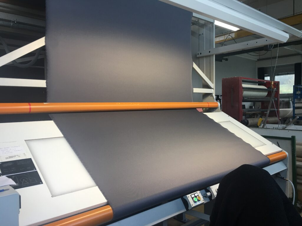 After the fabric is made, it is inspected on a workbench. The workbench is about two meters wide and has a backlit work surface as well as strong lights above. The inspector moves the fabric from one beam to another.