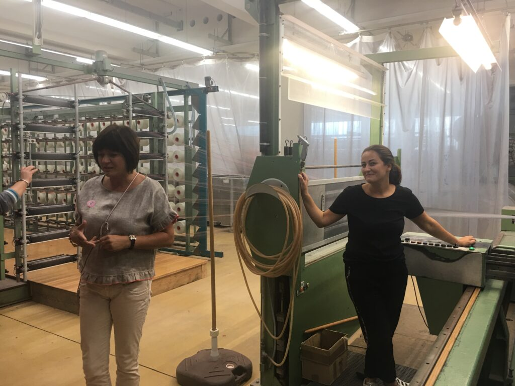 Two women stand in front of the drawing machine. It is painted in a muted green. Behind them is a large rack holding thread cones. The rack is the size of a small room.