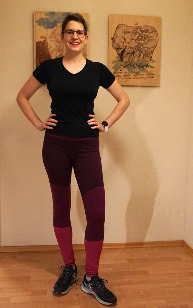 Bettina is seen from the front wearing her colorblocked Aila Leggings. The leggings have three shades of berry purple.