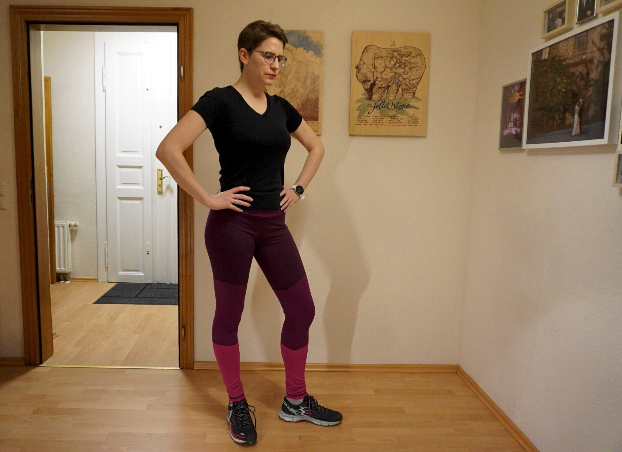 Bettina ist im Viertelprofil zu sehen. Sie trägt ein schwarzes T-Shirt und ihre Aila Leggings mit Colorblocking in drei Beerenfarben.