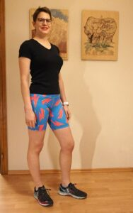Bettina is seen from the side-front. She's wearing a black t-shirt and her Aila Leggings in the bike short length. They reach the mid-thigh. The fabric is blue and covered in pink lightning bolts.