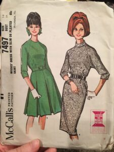 Pattern envelope for vintage McCall's 7497. Raglan sleeve dress with lightly bloused bodice and slim three-piece skirt, or box pleated four-piece skirt. Bodice is gathered in waistline seam at side front, has back pleat, may be lined. Slim dress has bias, turtle neck collar. Pleated skirt has seams and lining above pleats which start at about hipline. Either version has center back zipper.