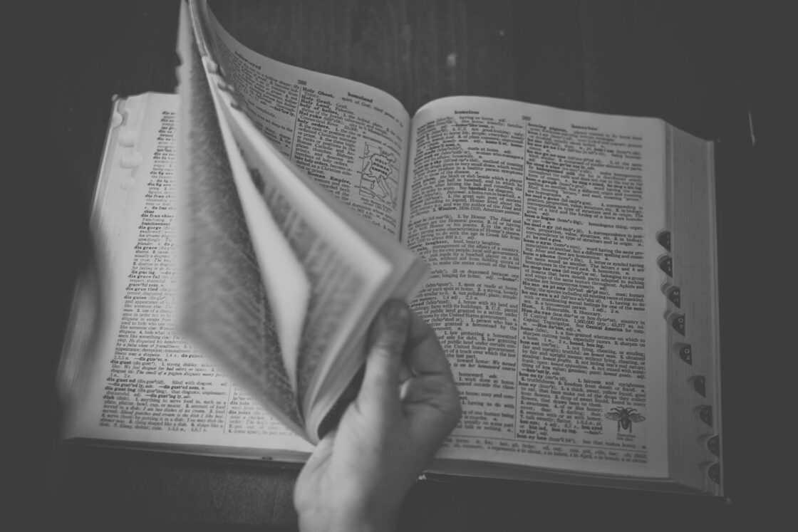 Black and white photo of a woman leafing through a dictionary