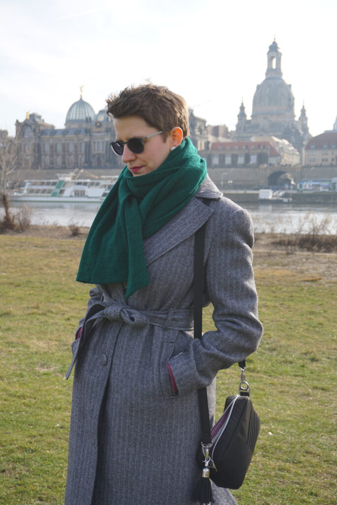 Bettina is seen from the side front in her Viki Sews Diana coat. She is looking down. In the background, you can see parts of the Dresden Old Town skyline.