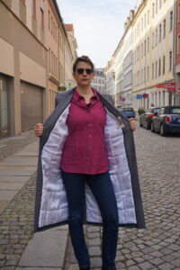 Bettina is standing and holding her Viki Sews Diana coat open with her hands. The lining, quilted white viscose satin, is visible.
