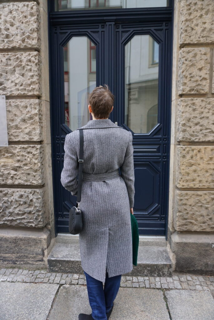 Bettina is seen from behind wearing her new Viki Sews Diana coat. She is standing in front of a dark blue door. The coat has a deep back vent and is cinched by a belt at the waist.