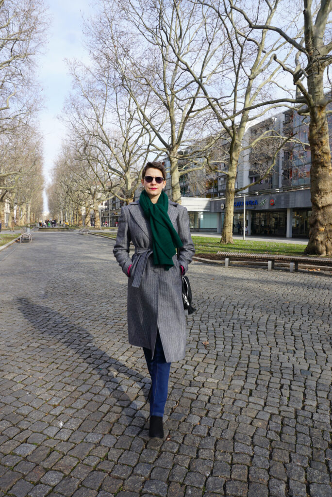 Bettina is wearing her new Viki Sews Diana coat. It is a black-andwhite herringbone tweed. Bettina is walking toward the camera and wearing a dark green knitted scarf.