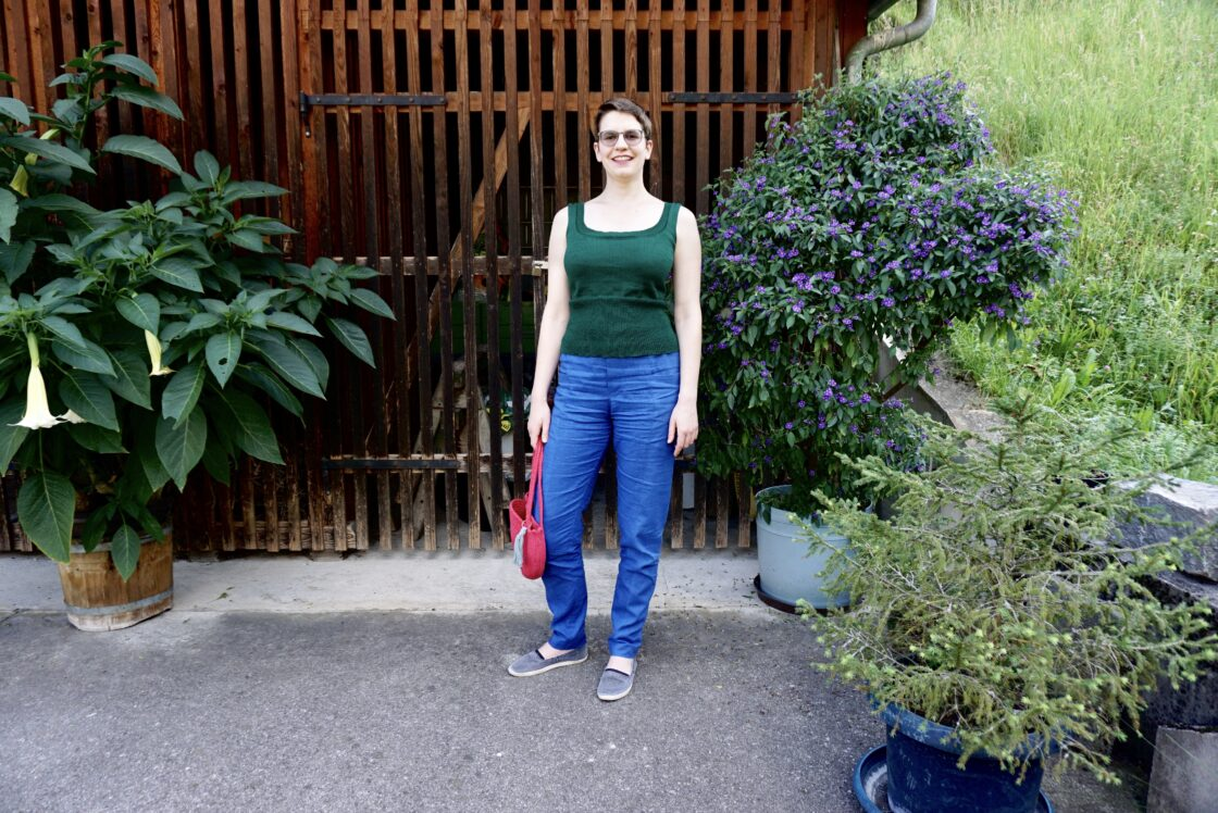 Bettina stands in front of a wood shed, looking at the camera. She's wearing royal blue pants, a green top and a pink purse.